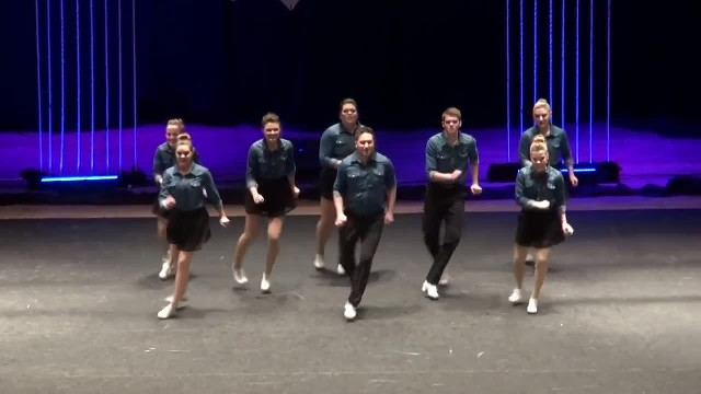 8 Dancers Line Up On Stage In Perfect Formation. When They Start Clogging, The Crowd Can't Look Away