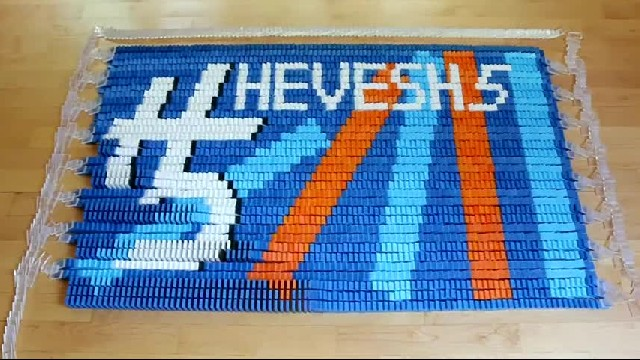 She spent 8 days meticulously stacking 15,000 dominoes — now watch them fall