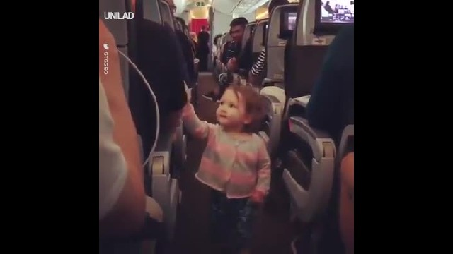 Tiny toddler has cutest way of making grumpy travelers smile on delayed flight
