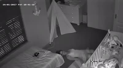 Dad is checking the security camera in his baby's nursery when he sees mom sliding on the ground