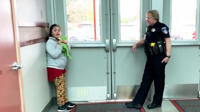 Officer helps calm young girl by singing to her in school hallway