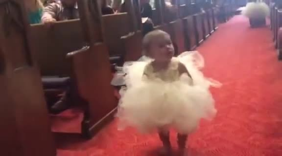 Flower girl scans aisles for familiar face, now watch her steal the show at sight of the groom