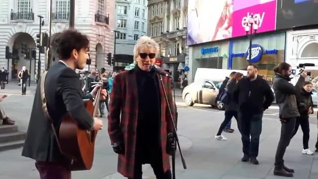 Man grabs mic from street performer and starts to sing. Crowd recognizes his voice and cheers