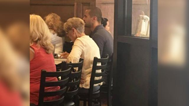 Elderly woman waits at restaurant for table for one. Suddenly, young man gets up, points to empty se