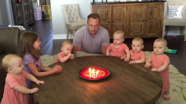 Sisters sing happy birthday to daddy, but watch baby on right when he blows out candles