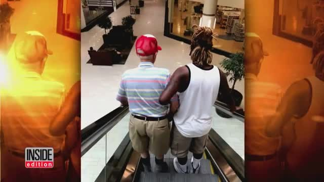 Young man sees grandpa struggling at top of escalator, approaches him with extended arm