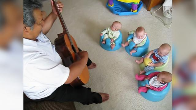 Granduncle plays guitar for his quadruplet grand-nieces and nephews.
