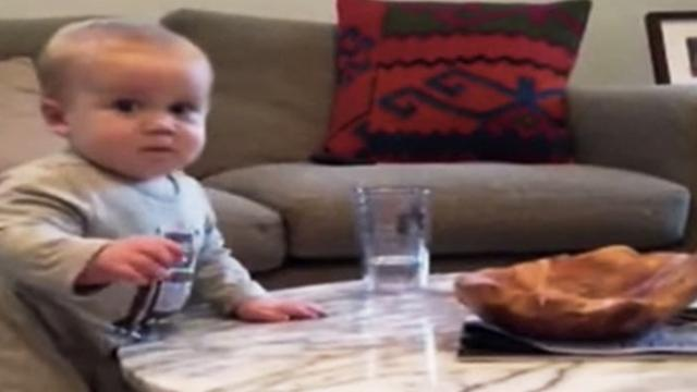 Mischievous baby reaches for water glass, but when mom yells 'no!' his face is priceless.