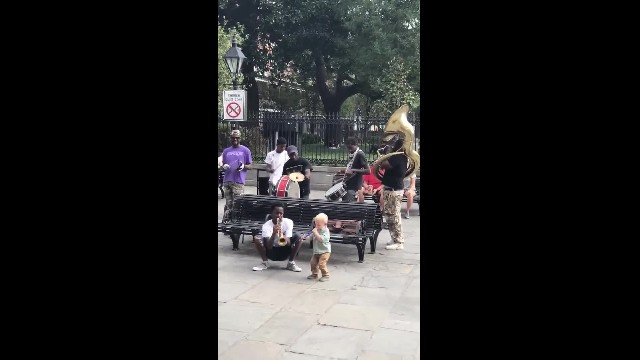 Toddler joins jazz band on street - immediately steals the show with fake trumpet
