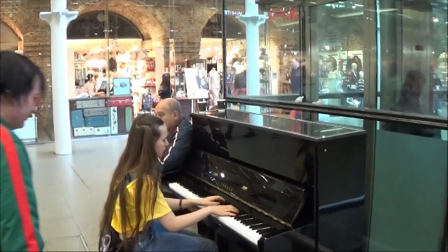 Man in green interrupts young girl on piano with stunt that causes crowd to immediately rush in