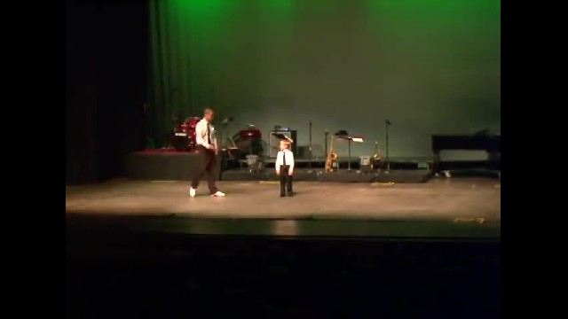 4-year-old steps on stage with instructor. Duo brings the house down with taping skills